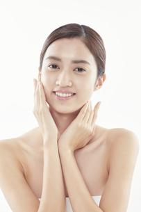 頬に手を添える日本人女性のビューティイメージの写真素材 [FYI04730396]