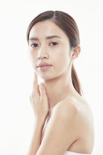 頬に手を添える日本人女性のビューティイメージの写真素材 [FYI04730398]