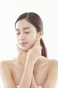 頬に手を添える日本人女性のビューティイメージの写真素材 [FYI04730399]