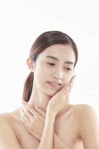 頬に手を添える日本人女性のビューティイメージの写真素材 [FYI04730401]