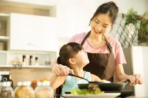 キッチンで母親といっしょにご飯を作っている小さい女の子の写真素材 [FYI04730466]