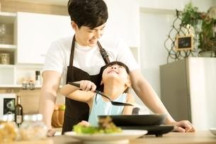 キッチンで父親といっしょにご飯を作っている小さい女の子の写真素材 [FYI04730467]