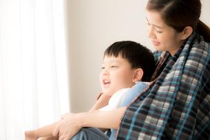 母親と息子がいっしょにブランケットに入って遊んでいるの写真素材 [FYI04730470]