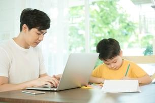 パソコンで仕事している父親の横でお描きしている男の子の写真素材 [FYI04730471]