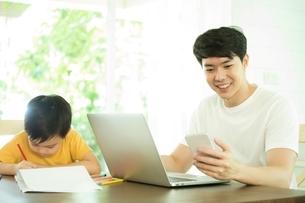 パソコンで仕事している父親の横でお描きしている男の子の写真素材 [FYI04730472]