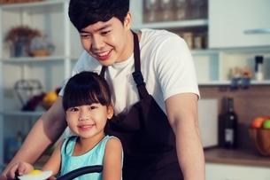 キッチンで父親といっしょにご飯を作っている小さい女の子の写真素材 [FYI04730474]