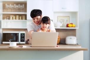 父親にパソコンを教わっている小さい女の子の写真素材 [FYI04730478]