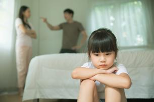 両親が喧嘩して冴えない表情の小さい女の子の写真素材 [FYI04730480]