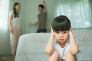 喧嘩している両親の怒鳴り声が聞こえないように耳をふさぐ女の子の写真素材 [FYI04730481]