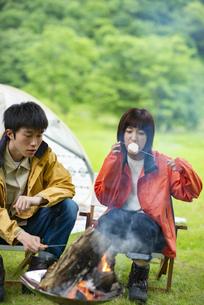 焚き火でマシュマロを焼くカップルの写真素材 [FYI04730652]
