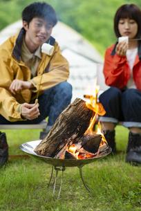 焚き火でマシュマロを焼くカップルの写真素材 [FYI04730657]
