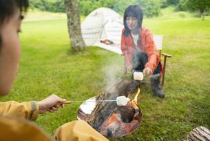 焚き火でマシュマロを焼くカップルの写真素材 [FYI04730664]