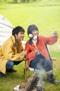 キャンプ場で自撮りをするカップルの写真素材 [FYI04730704]