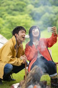キャンプ場で自撮りをするカップルの写真素材 [FYI04730706]