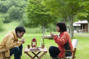 キャンプ場で飲食をするカップルの写真素材 [FYI04730763]