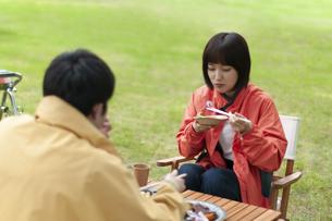 キャンプ場で飲食をするカップルの写真素材 [FYI04730764]