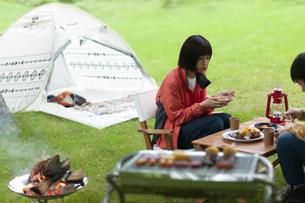 キャンプ場で飲食をするカップルの写真素材 [FYI04730766]