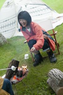 焚き火でマシュマロを焼くカップルの写真素材 [FYI04730781]