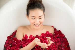 バラの花びらがいっぱい入っているバスタブに入浴している女性の写真素材 [FYI04730857]