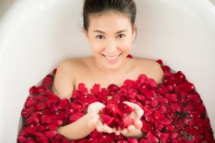 バラの花びらがいっぱい入っているバスタブに入浴している女性の写真素材 [FYI04730859]