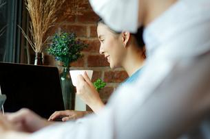 カフェでパソコンをしながらコーヒーを楽しむ若い女性の写真素材 [FYI04730861]