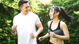公園でランニングしている若いカップルの写真素材 [FYI04730942]