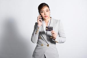 携帯電話をかけながらクレジットカードを見せる若い女性の写真素材 [FYI04731234]
