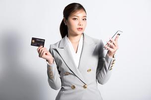 クレジットカードと携帯電話を両手に持つ綺麗な若い女性の写真素材 [FYI04731238]