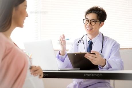 妊婦にアドバイスする若い男性医師の写真素材 [FYI04731288]