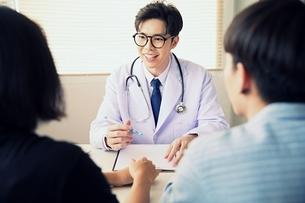 カップルにアドバイスをしている若い男性医師の写真素材 [FYI04731293]