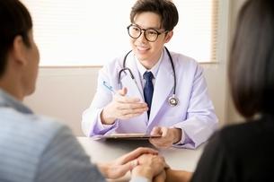 カップルにアドバイスをしている若い男性医師の写真素材 [FYI04731294]