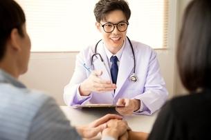 カップルにアドバイスをしている若い男性医師の写真素材 [FYI04731295]