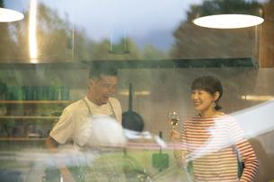 共同キッチンで談笑する男女の写真素材 [FYI04731635]