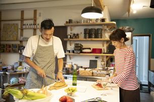 共同キッチンで調理する男女の写真素材 [FYI04731637]