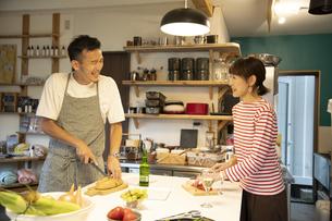 共同キッチンで調理する男女の写真素材 [FYI04731638]