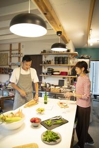 共同キッチンで調理する男女の写真素材 [FYI04731643]