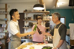 共同キッチンで談笑する男女の写真素材 [FYI04731648]