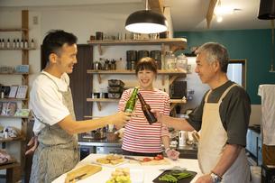 共同キッチンで談笑する男女の写真素材 [FYI04731652]
