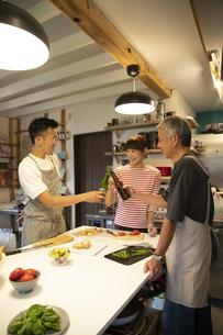 共同キッチンで談笑する男女の写真素材 [FYI04731669]