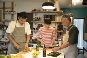 共同キッチンで調理する男女の写真素材 [FYI04731675]