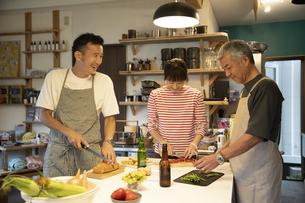 共同キッチンで調理する男女の写真素材 [FYI04731678]