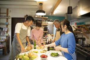 共同キッチンで調理する男女の写真素材 [FYI04731698]