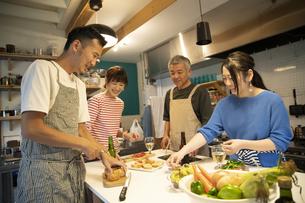 共同キッチンで調理する男女の写真素材 [FYI04731707]