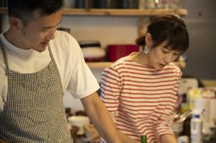 共同キッチンで調理する男女の写真素材 [FYI04731709]