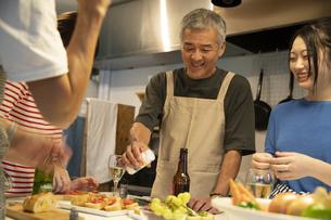 共同キッチンで調理する男女の写真素材 [FYI04731720]