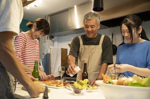 共同キッチンで調理する男女の写真素材 [FYI04731722]