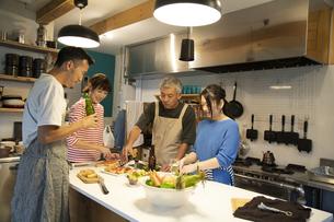 共同キッチンで調理する男女の写真素材 [FYI04731723]
