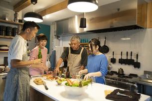 共同キッチンで調理する男女の写真素材 [FYI04731724]