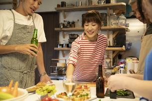 共同キッチンで調理する男女の写真素材 [FYI04731736]