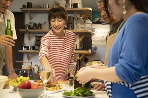 共同キッチンで調理する男女の写真素材 [FYI04731739]
